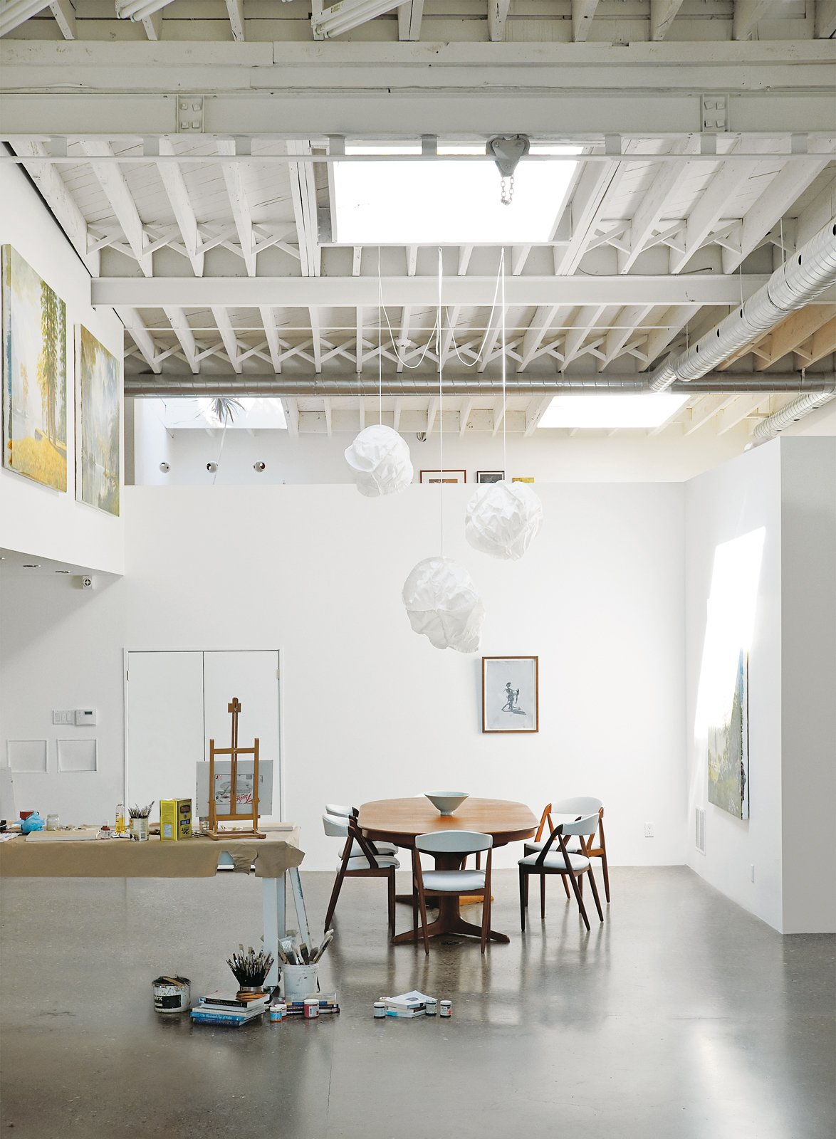 Inside, white paint lightens up the middle of the building. A vintage Danish dining set and Cloud pendants by Frank Gehry for Vitra define the dining area. Tagged: Dining Room, Chair, Table, Pendant Lighting, and Concrete Floor.  Photo 4 of 9 in An Art Studio That Would Make Picasso Jealous