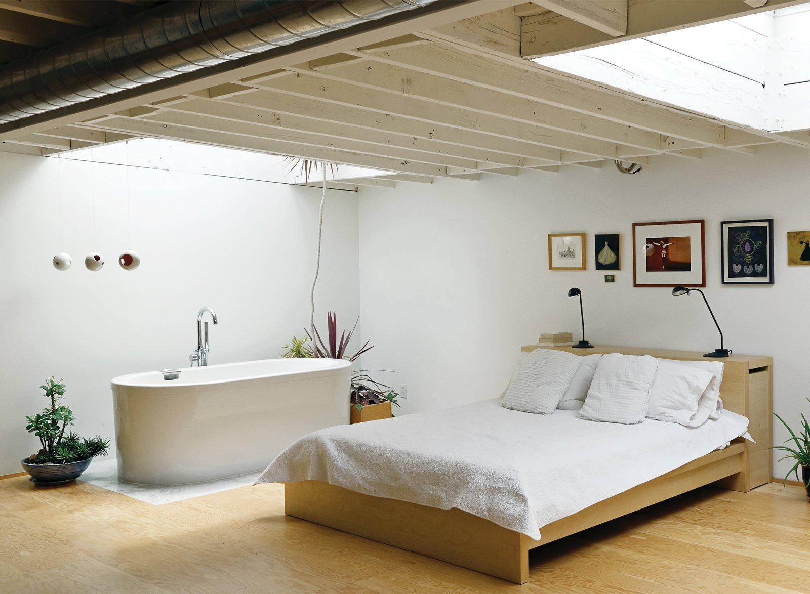 The bedroom mixes a bed and lamps from Ikea with a deep, luxurious bathtub (an inexpensive model from Neptune). The artworks include original prints by New York artist Franco Mondini-Ruiz.  Photo 9 of 9 in An Art Studio That Would Make Picasso Jealous