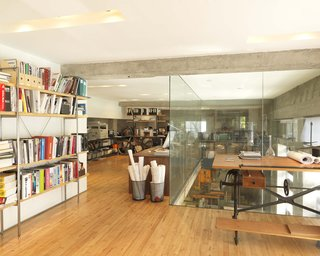 On the second floor, Larissa's office space looks over the workshop via a 20-foot-tall glass-enclosed shaft that lets lights in and accommodates behemoth projects.