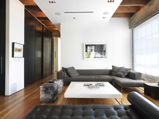 The open plan, high ceilings, and white walls all amplify the light that streams into the living room, accented with a Barcelona Couch by Mies van der Rohe for Knoll and two Blythe Pony Cube ottomans by Gus Design.