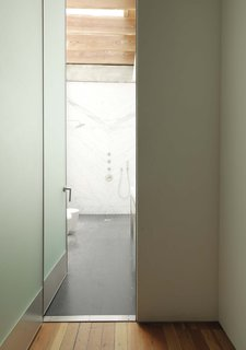 The hallway terminates in the bathroom, flooded in natural light.