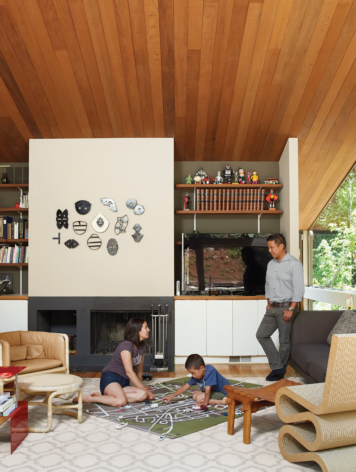 As his parents look on, Apolo plans his commute under a fire-top piece by the artist Michael Ricardo Andreev and alongside a Wiggle chair by Frank Gehry. Tagged: Living Room, Chair, End Tables, Light Hardwood Floor, Standard Layout Fireplace, Sofa, and Stools.  Photo 6 of 19 in Undivided Intentions