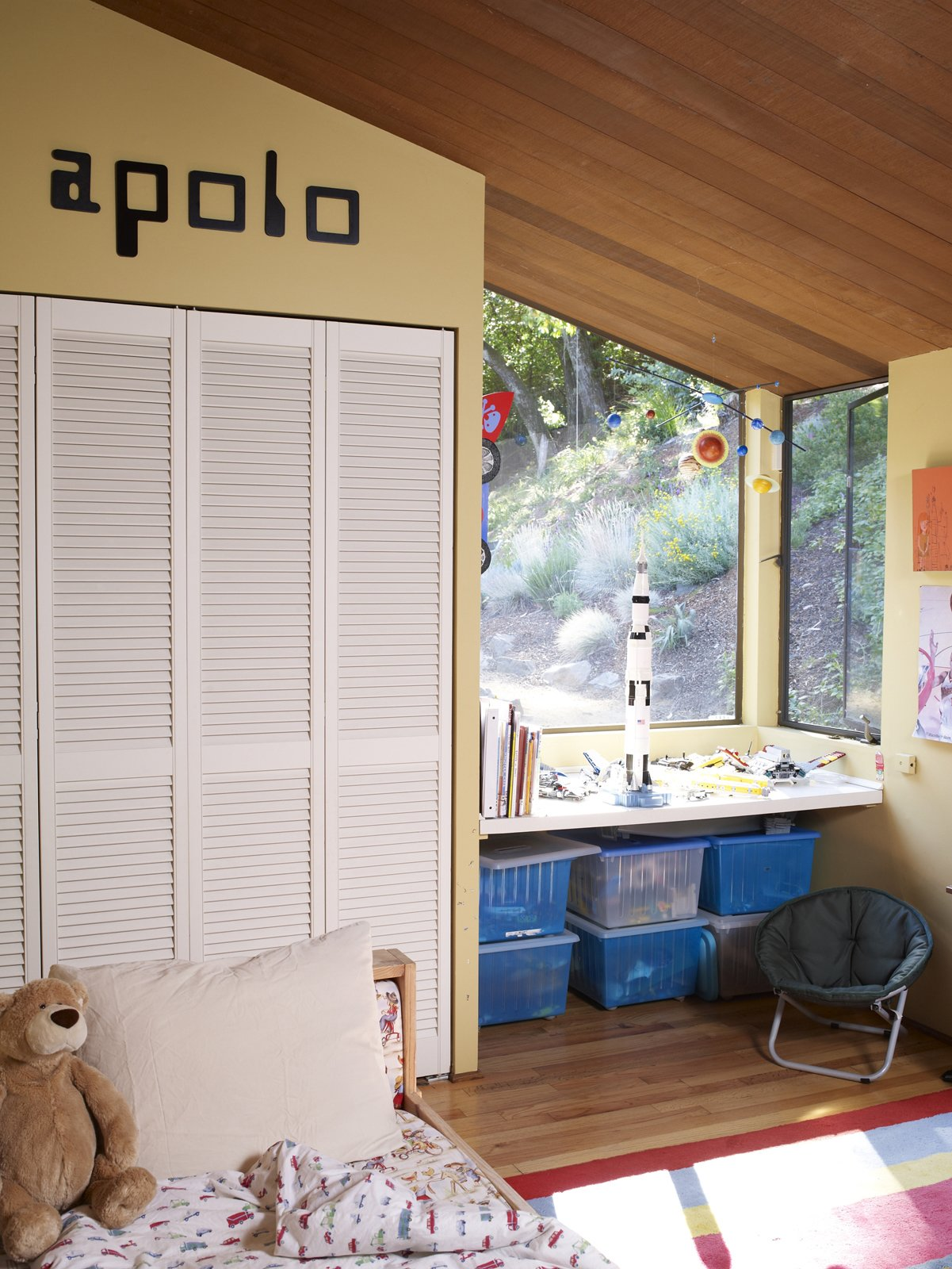 Apolo's bedroom is unmistakably that of a young boy, as the old-school computer font and clear debt to NASA suggest. Tagged: Kids Room, Bedroom, Bed, Chair, Storage, Desk, Boy Gender, and Light Hardwood Floor.  Photo 12 of 19 in Undivided Intentions
