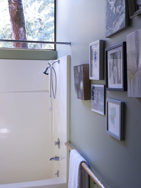 A salon-style hanging of art and the wooden handrail-cum-towel rack give the bathroom a handful of subtly stylish touches.