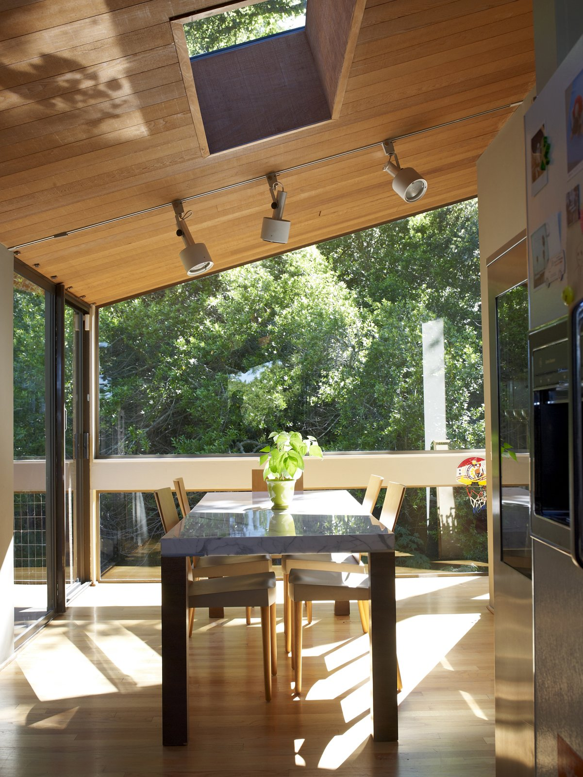 The family is never far from the outdoors, as this lush view from the dining room attests. Tagged: Dining Room, Table, and Chair.  Photo 16 of 19 in Undivided Intentions