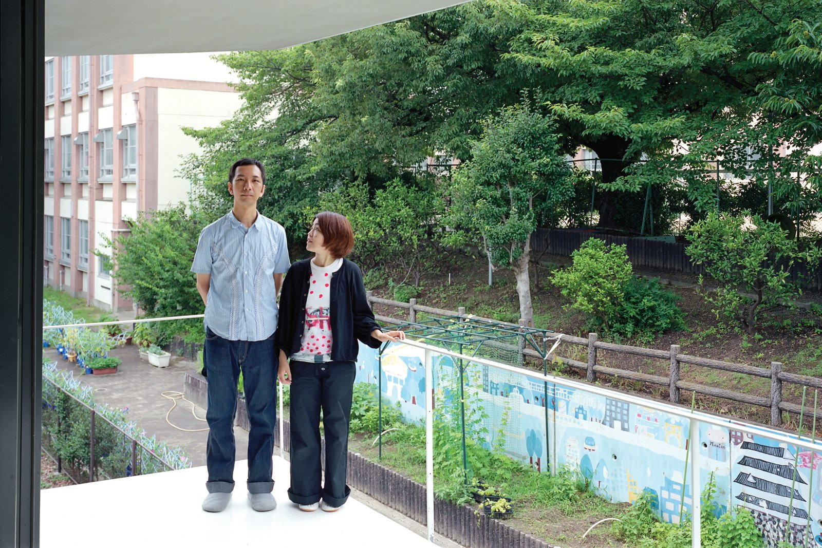 Without a garden of their own, Takuya and Yurika enjoy the verdant view of the schoolyard cherry trees next door from their bedroom balcony.  Photo 4 of 11 in Small Space Live/Work Box Home in Japan
