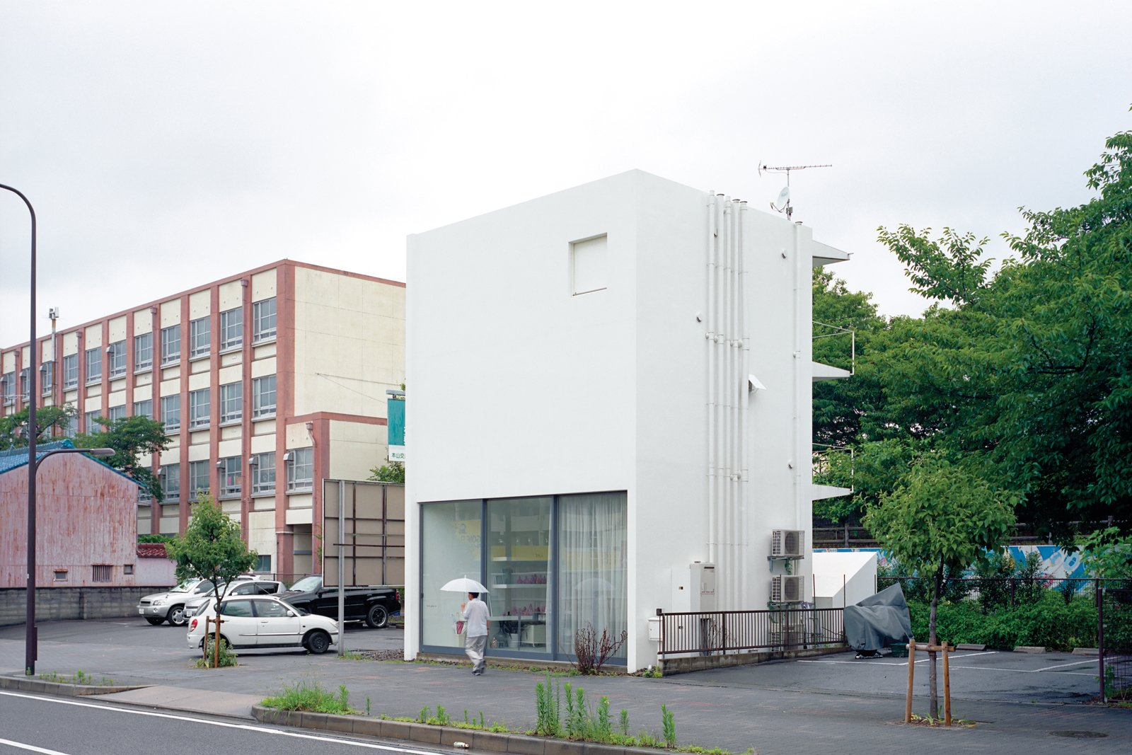 The structure is an elegant riff on the boxy apartments and school that surround it.  Photo 6 of 11 in Small Space Live/Work Box Home in Japan