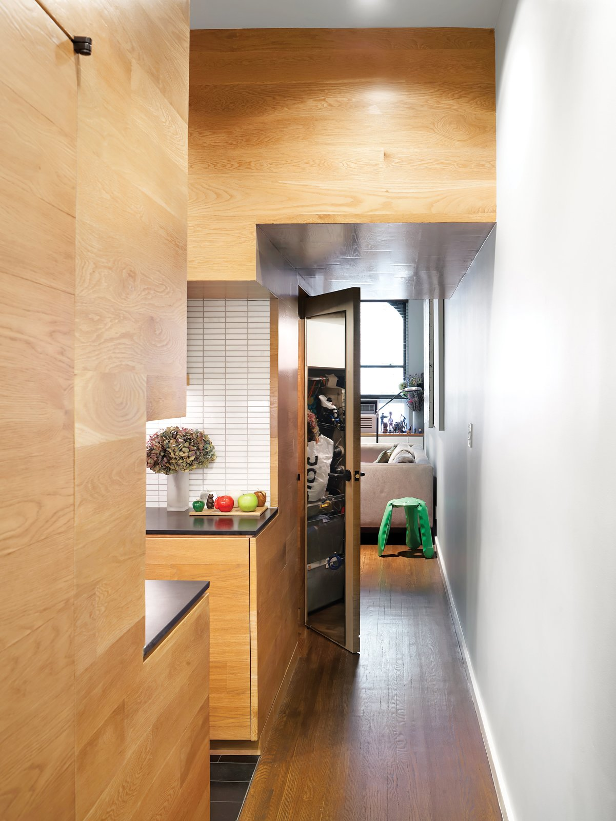 White oak paneling imbues uniformity and warmth into the hallway, kitchen, and living spaces. Tagged: Kitchen, Wood Cabinet, Ceramic Tile Backsplashe, and Medium Hardwood Floor.  Photo 4 of 12 in The Manhattan Transformation
