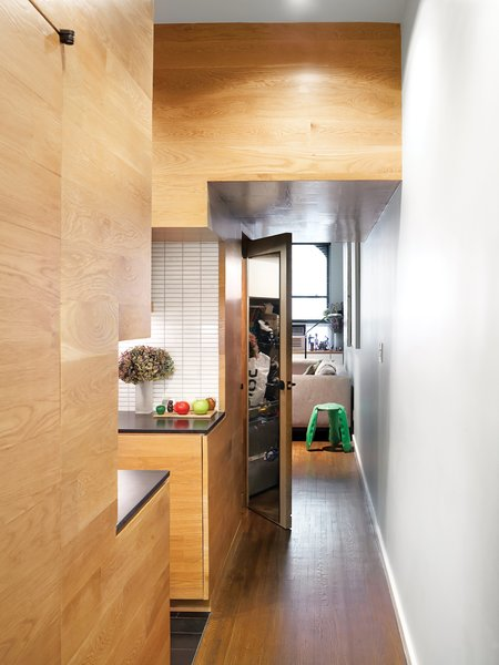 White oak paneling imbues uniformity and warmth into the hallway, kitchen, and living spaces.
