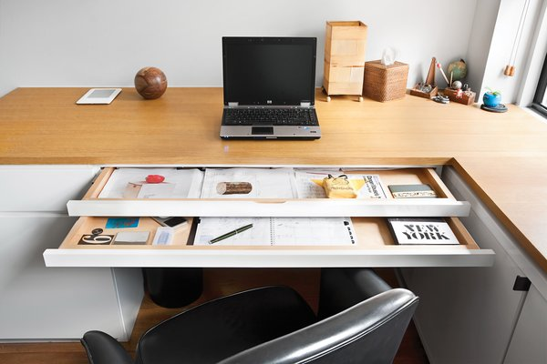 Each of the sliding trays in Pozner's tidy office desk serves a different function.
