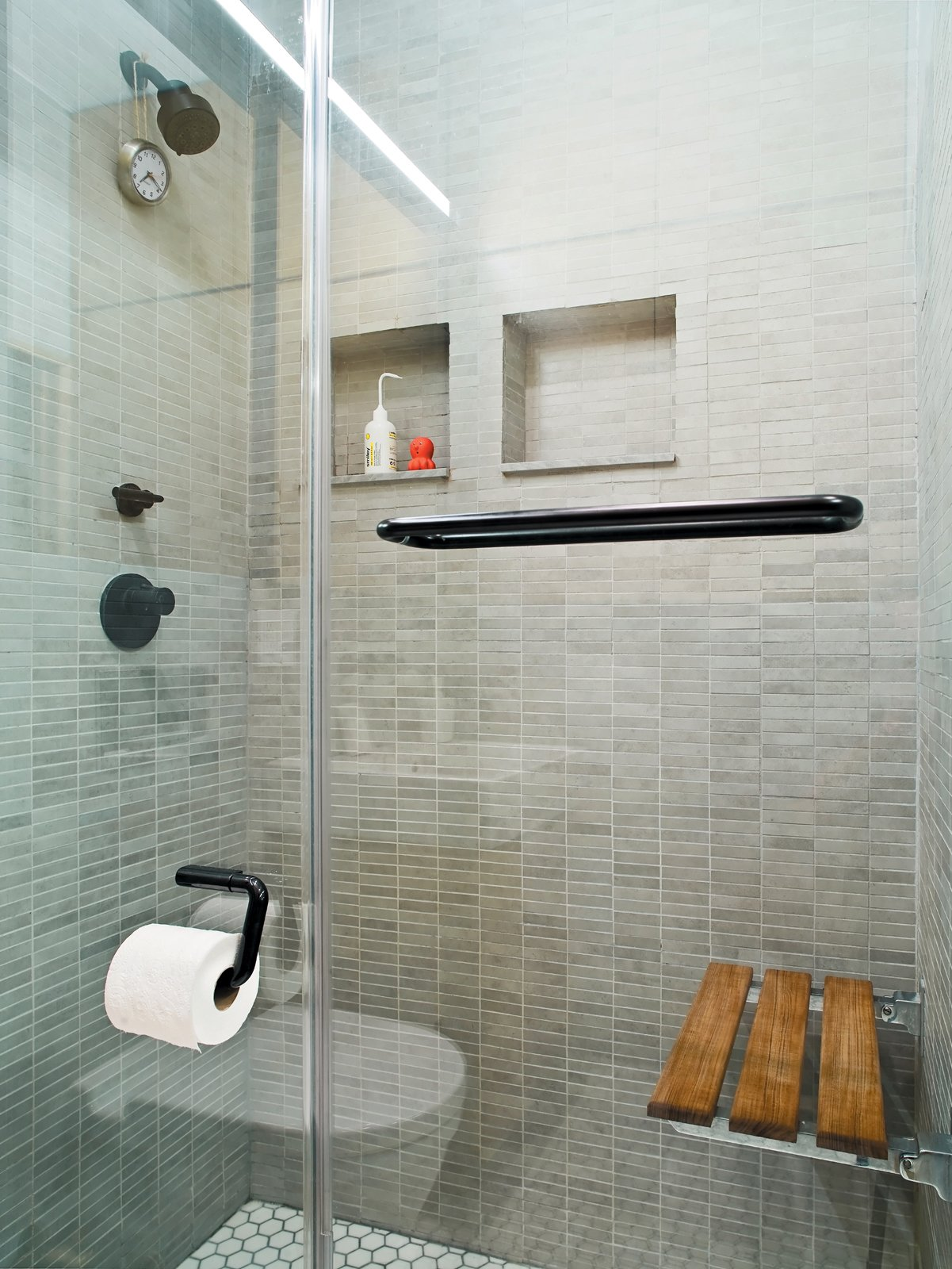 """I got rid of the bathtub because I like the idea of a big shower,"" Pozner explains. But to achieve a comparable effect, he installed a teak bench from Waterworks on the rear shower wall. ""One of the things I like about a bath is that you can soak. Here I can sit and have the water pound on me—it's a hybrid shower and bath."" Tagged: Bath Room and Enclosed Shower.  Photo 10 of 12 in The Manhattan Transformation"