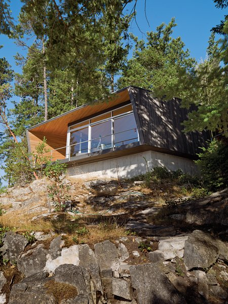 Perched over a cliff face, the hooded deck of the Gambier Residence reads like a ship's prow over Howe Sound, the scenic waters near Vancouver. Tagged: Exterior, House, Cabin Building Type, Flat RoofLine, and Wood Siding Material.  Photo 51 of 101 in 101 Best Modern Cabins from Modern Cantilevered Homes