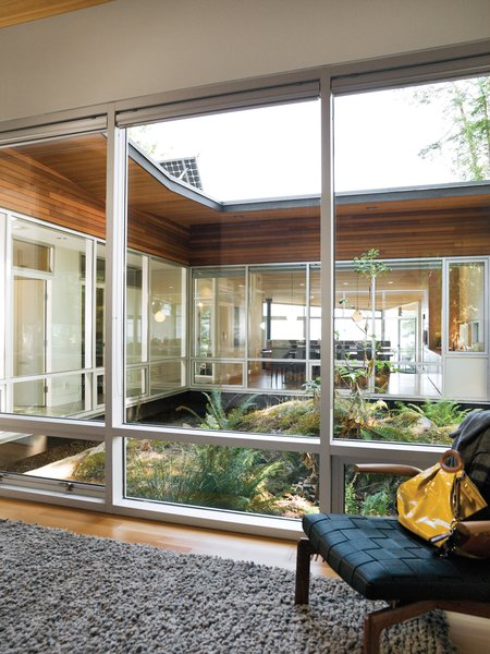 The plan of the house revolves around a rocky outcropping lush with life that acts as the home's central atrium. The granite was left intact in order to serve as the nucleus of the courtyard, and the walls of windows draw a wealth of natural daylight into the back of the building.