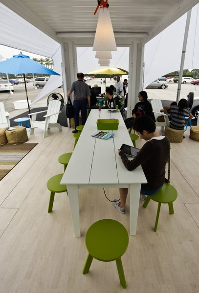 A portion of the main outdoor area features flooring by Lonseal, outdoor furniture by Loll Designs, West Elm ottomans, and flexible bins by Tubtrugs.