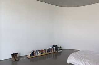 Keener's bedroom contains a bed, a pair of boots, and a selection of books—and nothing else.