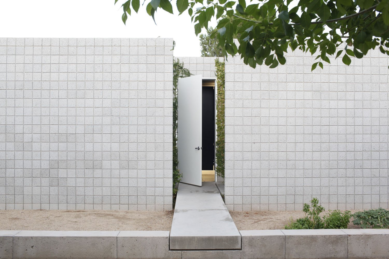 The front door is accessed by a 'floating' concrete bridge that bisects the two wings of the house. Take a Peek Through These 10 Modern Front Doors - Photo 5 of 10