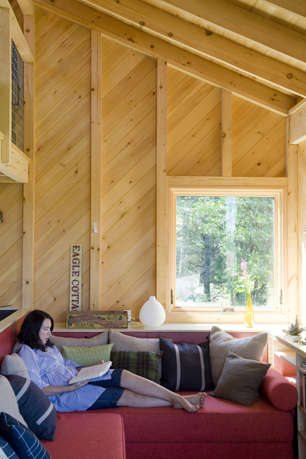 Alex relaxes on the first-floor couch, with is filled with an array of pillows from Crate and Barrel, CB2, West Elm, Muji, and Blu Dot.  Photo 14 of 21 in A Tiny Cabin is This Writer's Off the Grid Getaway