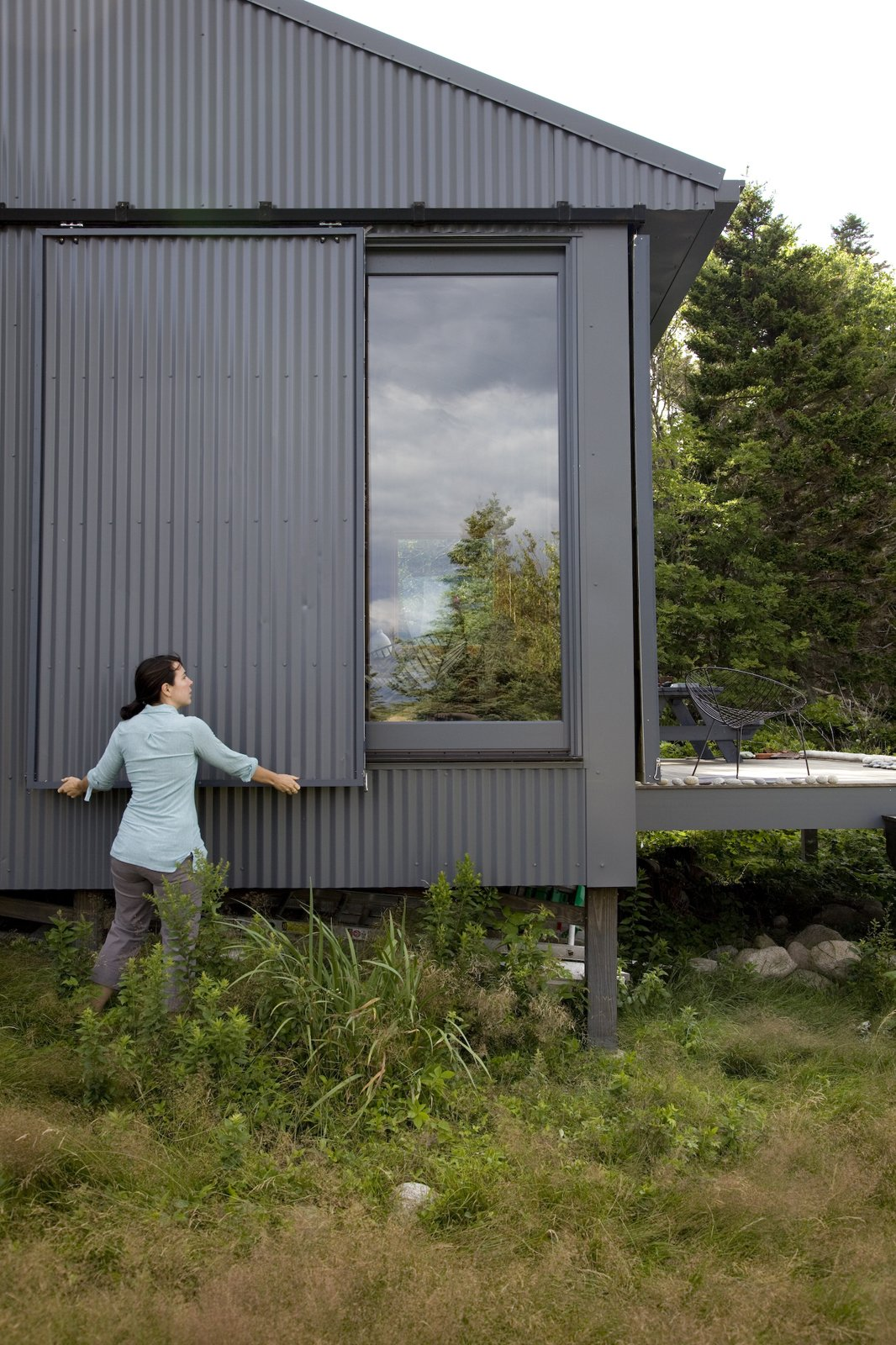 When Alex or Bruce leave the island, closing up shop is as simple as sliding panels of corrugated metal into place to protect the windows.  Photo 15 of 21 in A Tiny Cabin is This Writer's Off the Grid Getaway