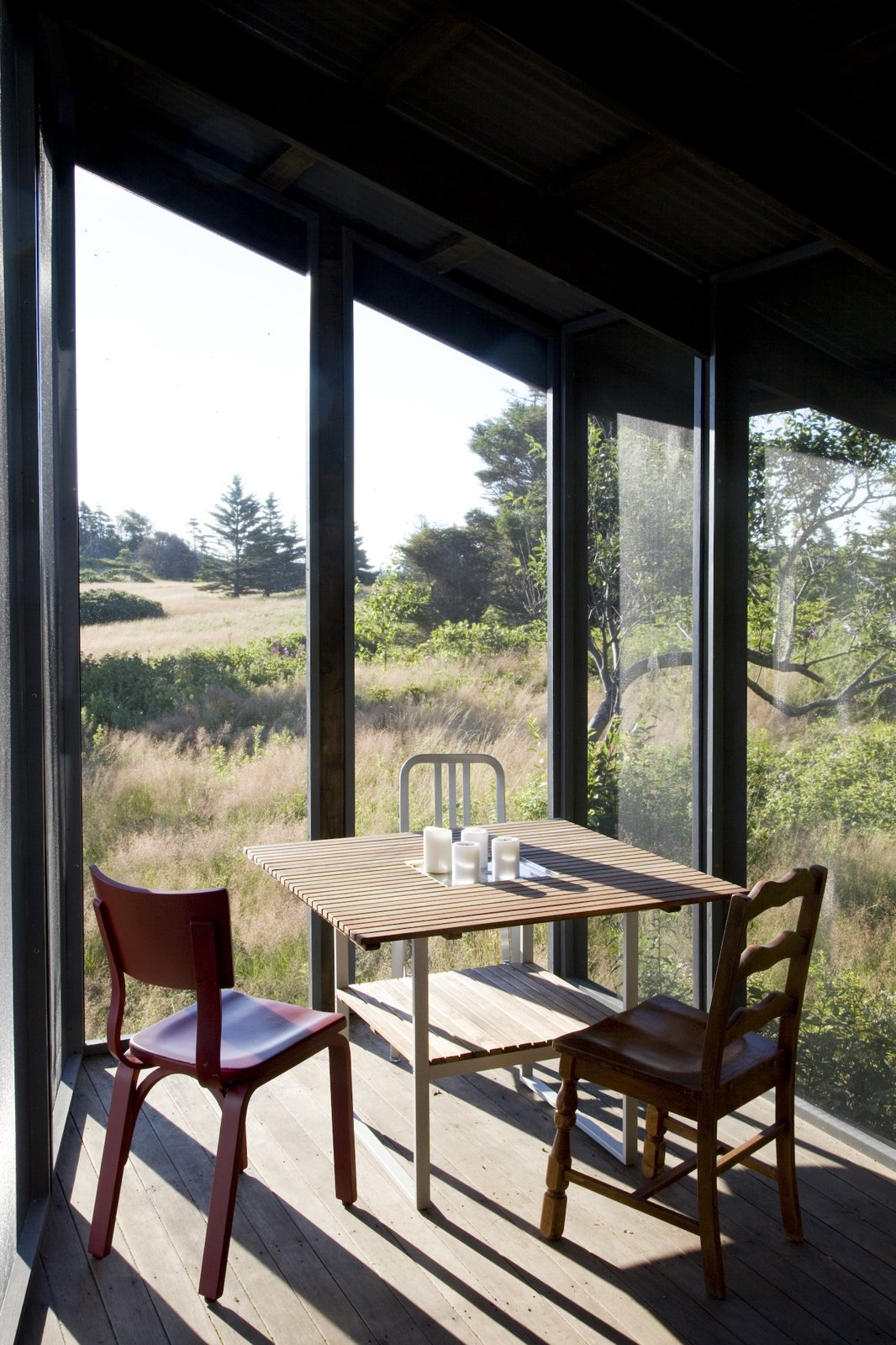 The screen porch serves as an auxiliary dining area and is furnished with a Teak outdoor table from Ikea surrounded by three chairs, including two vintage chairs and a silver 1006 Navy chair by Emeco from Design Within Reach.  Photo 16 of 21 in A Tiny Cabin is This Writer's Off the Grid Getaway