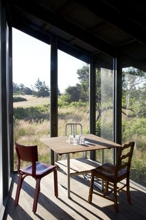 The screen porch serves as an auxiliary dining area and is furnished with a Teak outdoor table from Ikea surrounded by three chairs, including two vintage chairs and a silver 1006 Navy chair by Emeco from Design Within Reach.