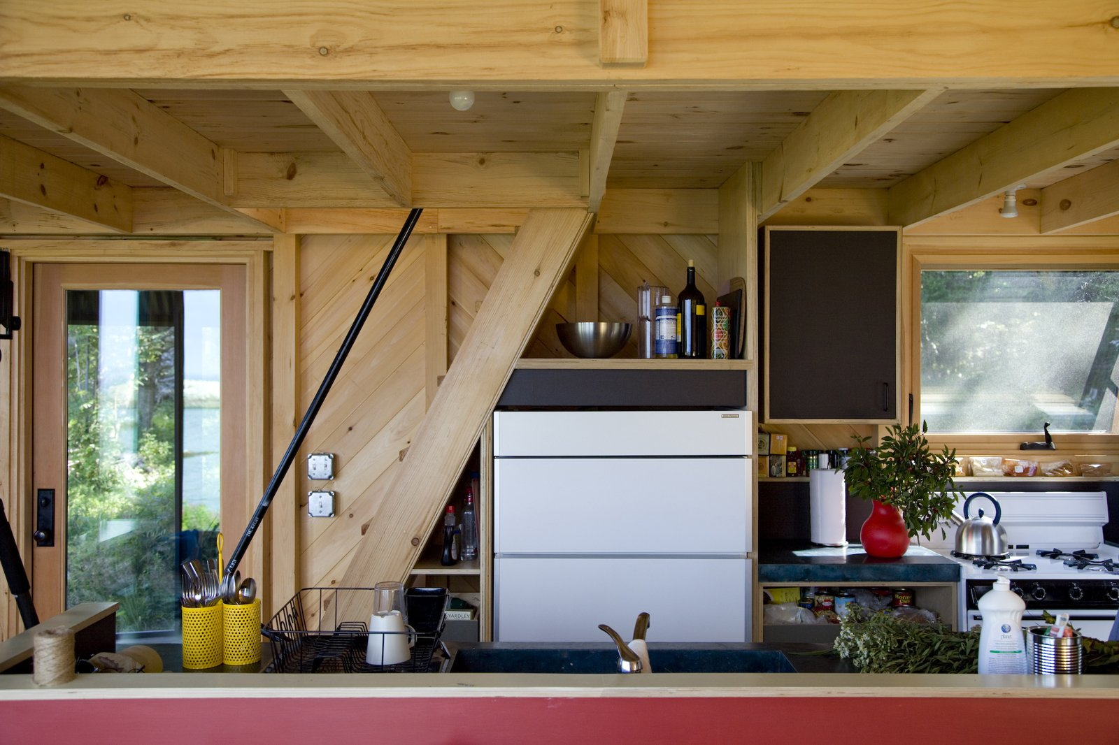 The Sunfrost refrigerator nearly disappears into the simple kitchen.  Photo 17 of 21 in A Tiny Cabin is This Writer's Off the Grid Getaway