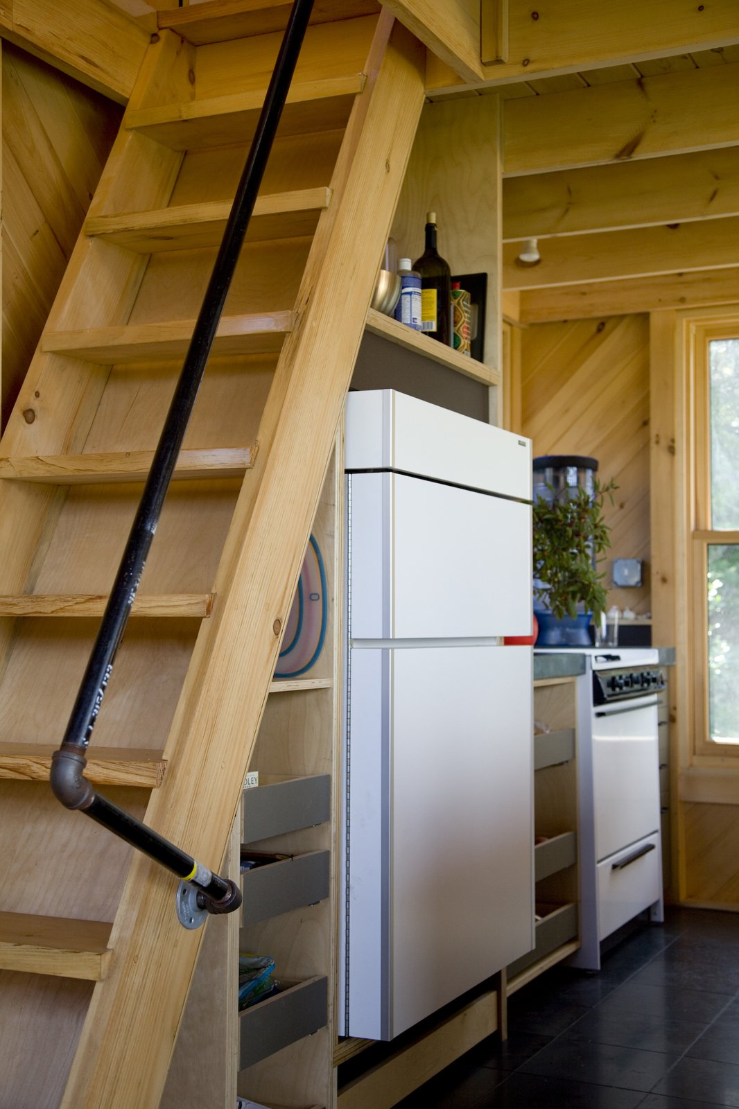 Howell was creative in his space-saving techniques as well as for practical matters. The handrail for the stairs to the loft was pieced together with lengths of PVC pipe and plumbing hardware.  Photo 21 of 21 in A Tiny Cabin is This Writer's Off the Grid Getaway