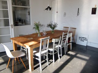 "The Sight Unseen gals' personal approach to coverage is evident in their thoughtfully curated slideshows. Khemsurov spent the summer staying at the Berlin loft shared by designers Judith Seng and  Alex Valder, and the following are a few shots from her stay (the entirety of which can be seen here). From Khemsurov : ""The apartment's huge kitchen offers seating for 10, on an assortment of found chairs Seng painted gray for a previous project. The pendant lamp was assembled by Valder from dual sockets he collected at American hardware stores."""