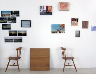 "Khemsurov: ""One of the living room walls hosts a makeshift art installation consisting of photos the pair took on a recent trip to New York, photos from past projects, gifts from friends, and in the upper right corner, their first art purchase — it's part of an art workshop a friend conducted with children in Africa. The chair halves were part of Seng's diploma project at school."""