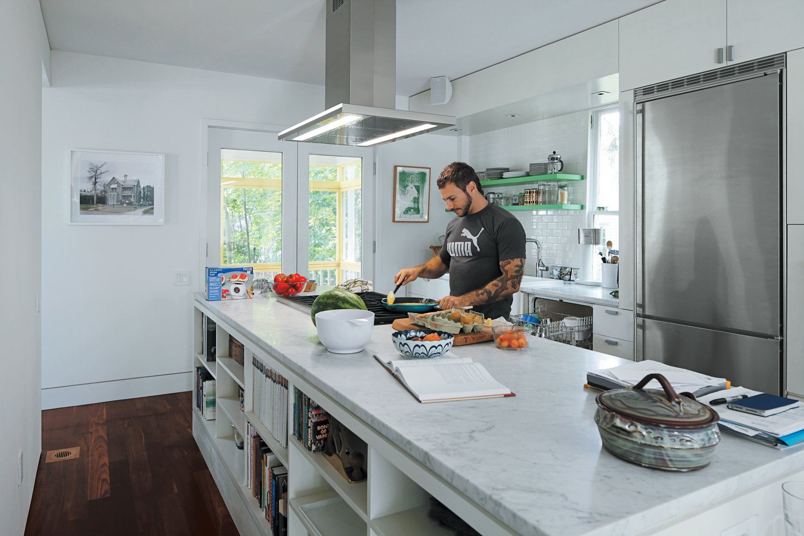 To accommodate his passion for cooking, Renaldi insisted on the long Carrara marble countertop, a niche for cookware, and ultra-contemporary appliances. Tagged: Kitchen, Marble Counter, Dark Hardwood Floor, Refrigerator, and Range.  Photo 6 of 11 in An 1850 schoolhouse in Milford, Pennsylvania