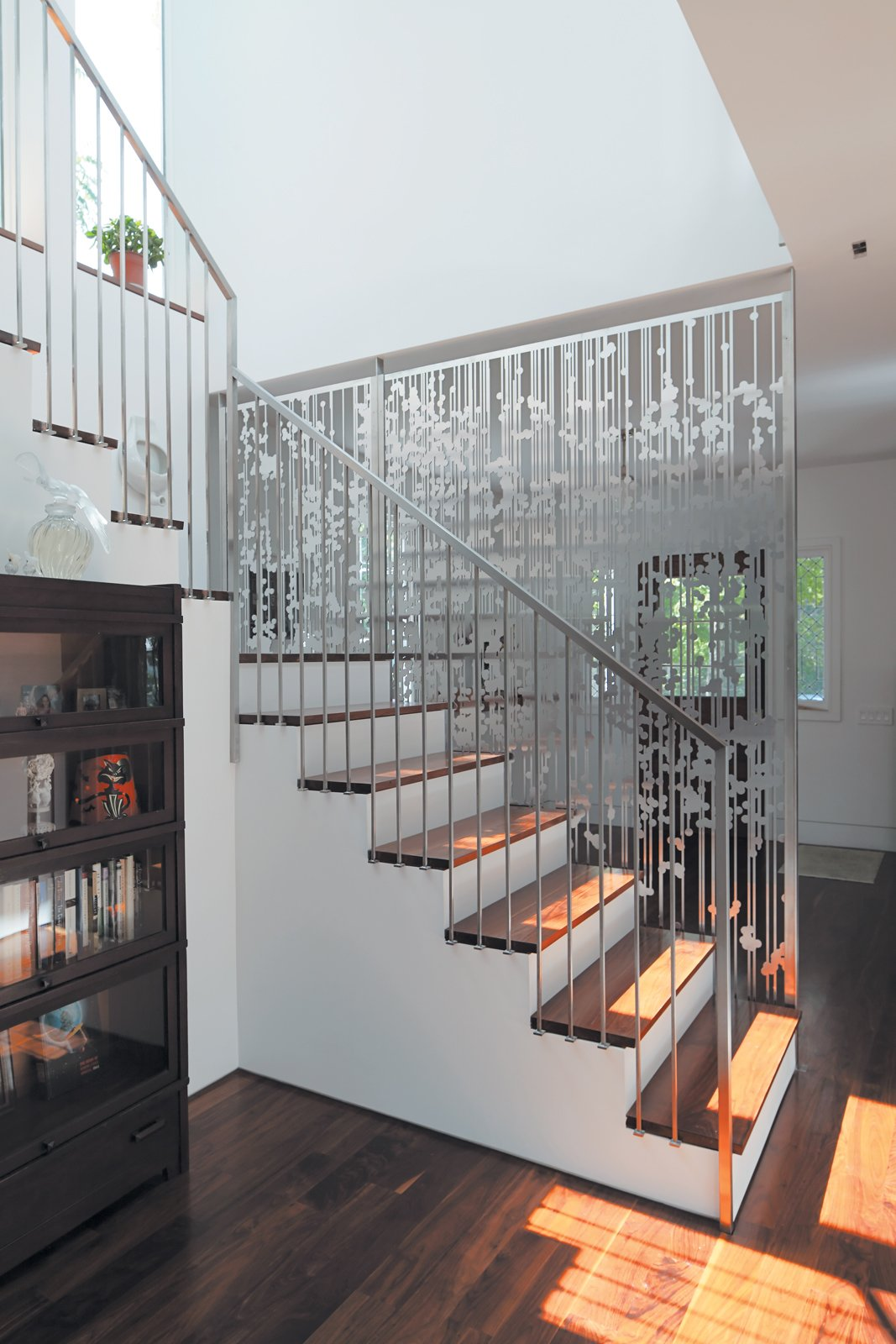Andrew Magnes's hanging screen composed of aluminum circles and lines, cut with a CNC water jet, separates the entry from the staircase and rear kitchen area. Tagged: Staircase and Wood Tread.  190+ Best Modern Staircase Ideas by Dwell from An 1850 schoolhouse in Milford, Pennsylvania