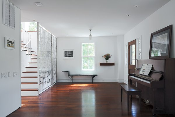 Combining old and new, Renaldi and Boyd placed the <br><br>latter's family piano and a painted metal Jean Prouvé bench in <br><br>the entryway, each a fine counterpoint to the filigree of Magnes's screen.