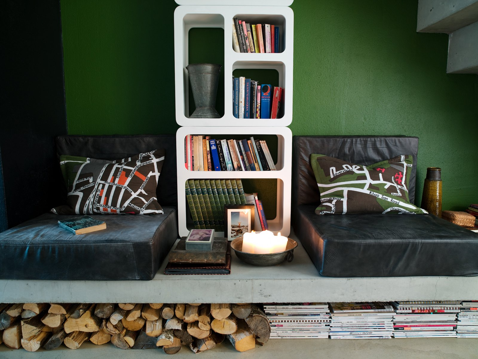 The reading corner can be turned into an extra bed. Schonning designed the leather poufs himself, and made the cushions from an Ikea carpet. Under the concrete slab there is room for wood, books and newspapers. Photo by Per Magnus Persson.  Storage by Dwell from An Attic Studio in Stockholm