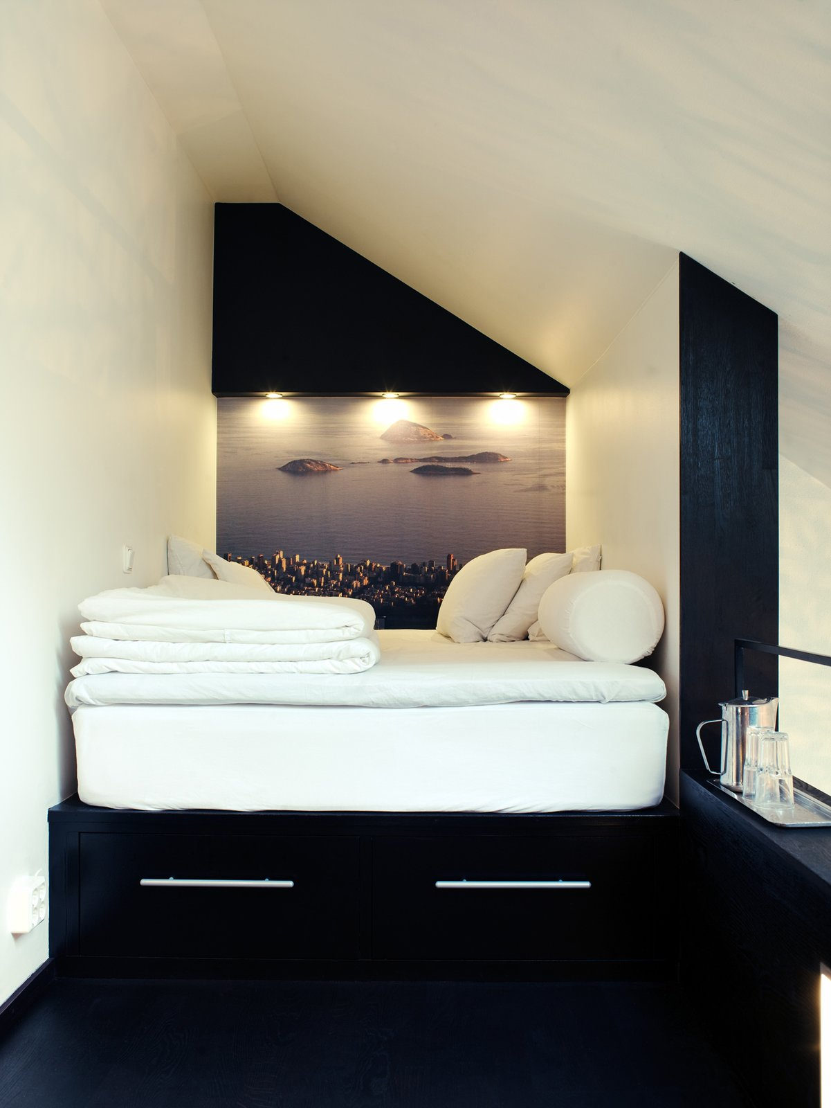 In the tiny sleeping loft is platform bed with two drawers beneath it. In place of wallpaper, Schonning enlarged a photograph he snapped in Rio de Janeiro. The inset spotlights and a small shelf at the end of the bed offer light and additional storage. Photo by Per Magnus Persson. Tiny Homes  by Erika Heet