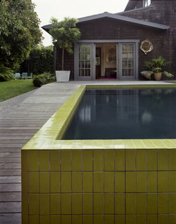 The wall that wraps around the sunken pool was completed—like the seeded concrete pathway—with painstaking precision. The tiles were custom designed with Mission Tile West to hit a pea-green hue and sized specifically to top the narrow walls.