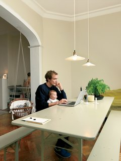 Thomas Lommee and baby Emilia Luz work at the beer-garden table under hanging lamps given to the couple by friends. The baby bassinet, which appears to be made from a wicker laundry basket and some sturdy rope, was also a gift from friends.