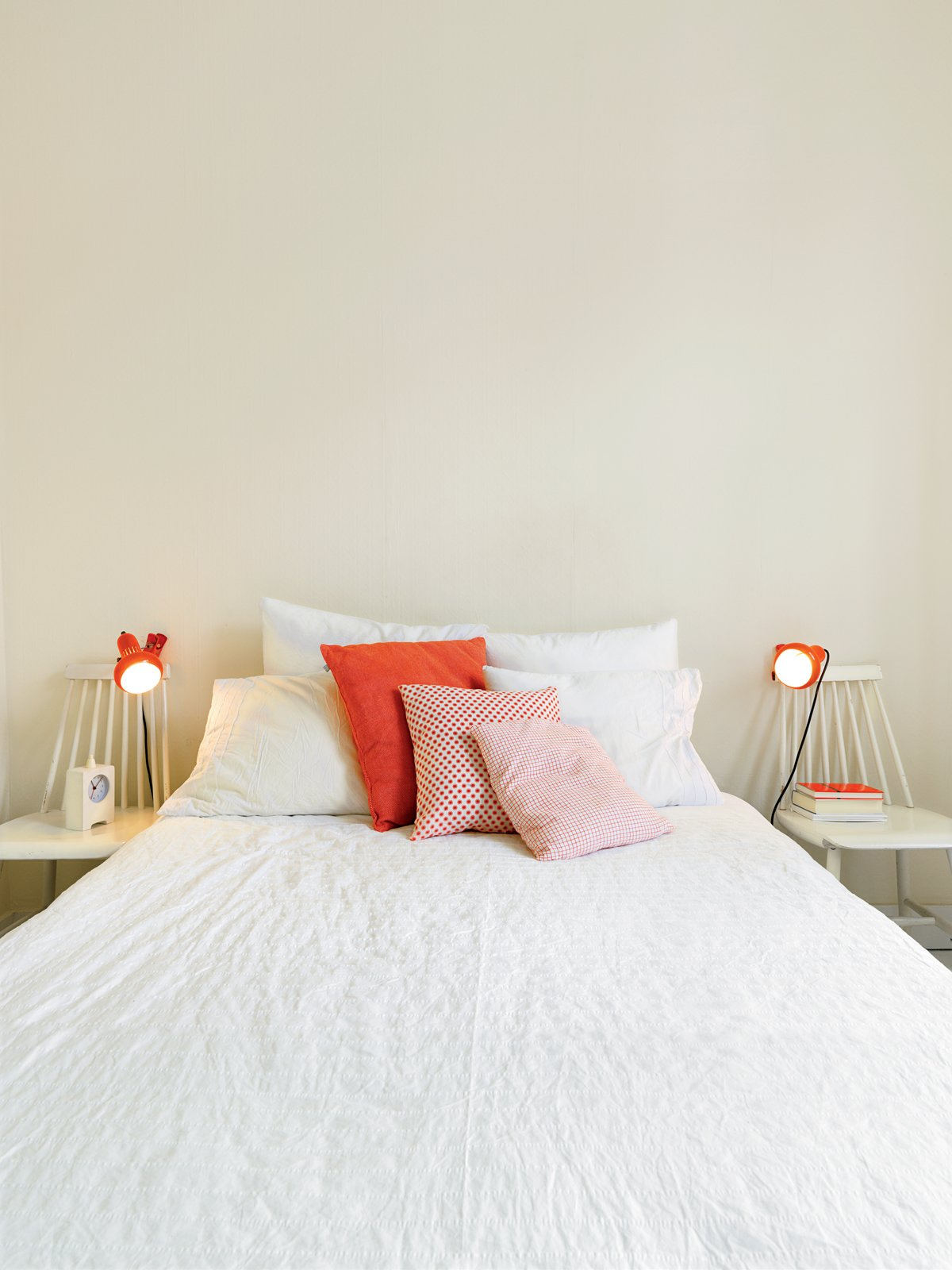 """The orange his-and-hers lamps in the bedroom came from Högner's sister's childhood bedroom. """"My sister prefers new things,"""" said Högner. """"But my dad can't throw anything out. Tagged: Bedroom, Bed, and Table Lighting.  Photo 9 of 15 in Kind of New"""
