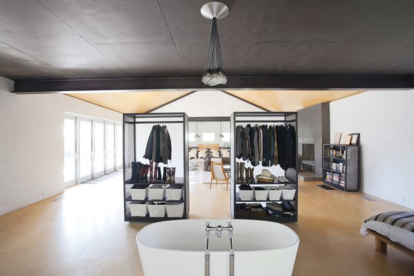 Hill's custom closets do double duty as both clothing receptacles and movable partitions, thanks to skateboard wheels affixed to their bases. Substantial enough to create a visual barrier but translucent to allow light through. the closets are backed by panels of formerly glossy white Plexiglas that Hill asked Sacaris to rough up with a piece of sandpaper.