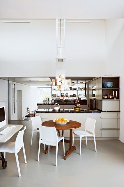 The kitchen frames a natural division between the public and private spaces of the house. The couple's private dining area features a round wooden table by Frank Bolink, and white chairs that are from Hema, a low-cost Dutch retailer.