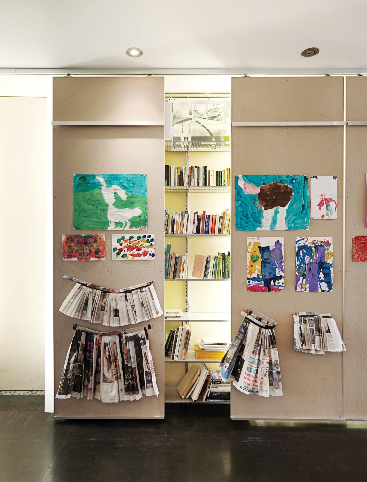 In the ground-floor gallery, 40-foot-long library shelving is punctuated by floor-to-ceiling columns made from white acrylic panels that conceal low-cost fluorescent-tube lighting. Tagged: Storage Room, Closet Storage Type, and Shelves Storage Type.  Photo 3 of 9 in Just Redo It