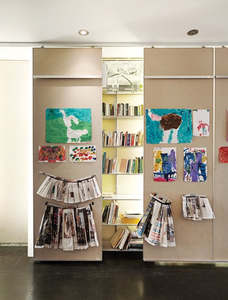 In the ground-floor gallery, 40-foot-long library shelving is punctuated by floor-to-ceiling columns made from white acrylic panels that conceal low-cost fluorescent-tube lighting.