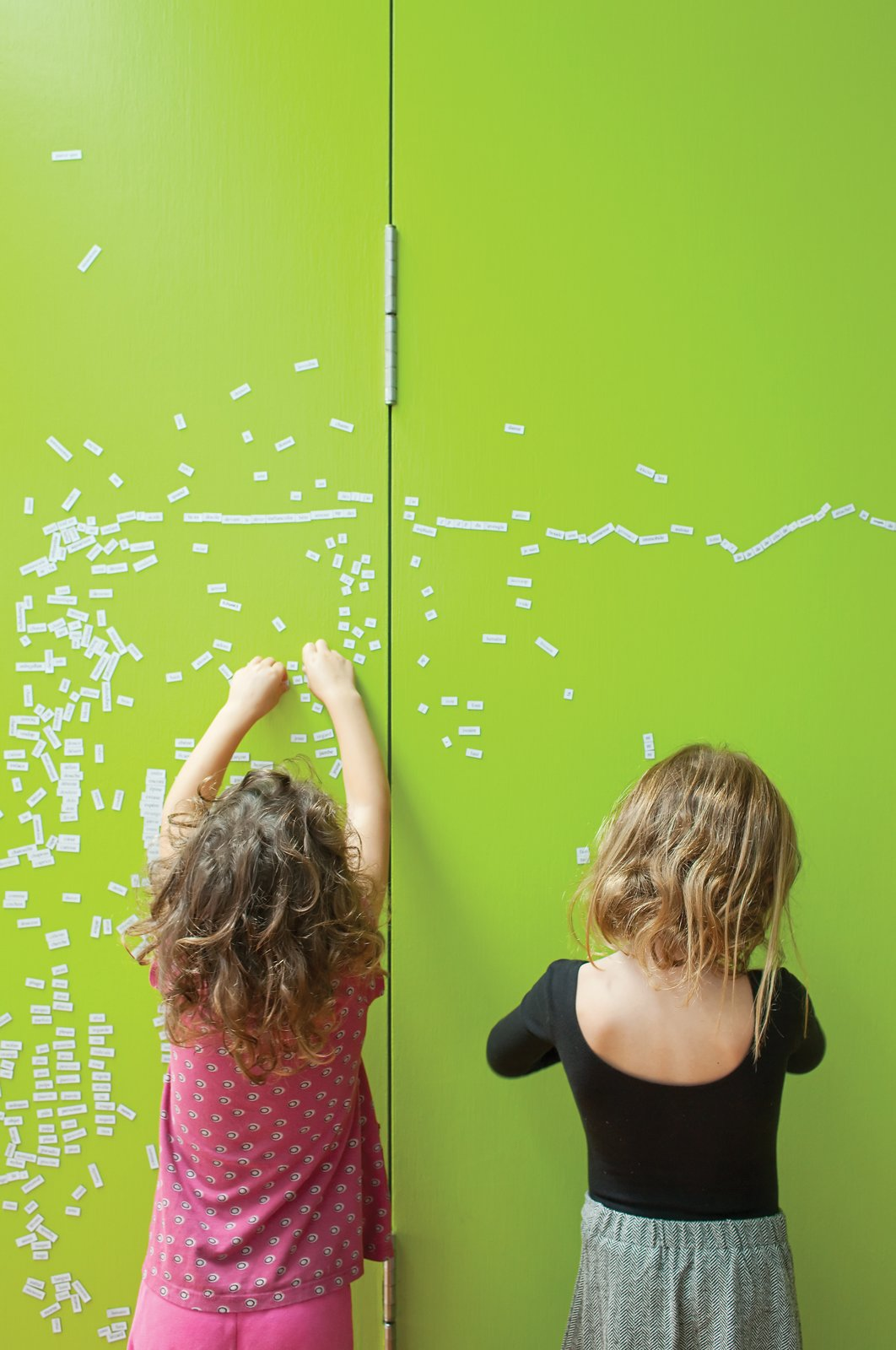 """The couple initially painted partition walls between the children's room and their own with black metallic paint creating both a writing surface for the children and a magnetic bulletin board for notes. However, """"the black looked too oppressive,"""" Astrakhan says. So they applied several coats of lively lime green paint to brighten up that section of the house. Tagged: Kids Room and Playroom.  Photo 5 of 9 in Just Redo It"""