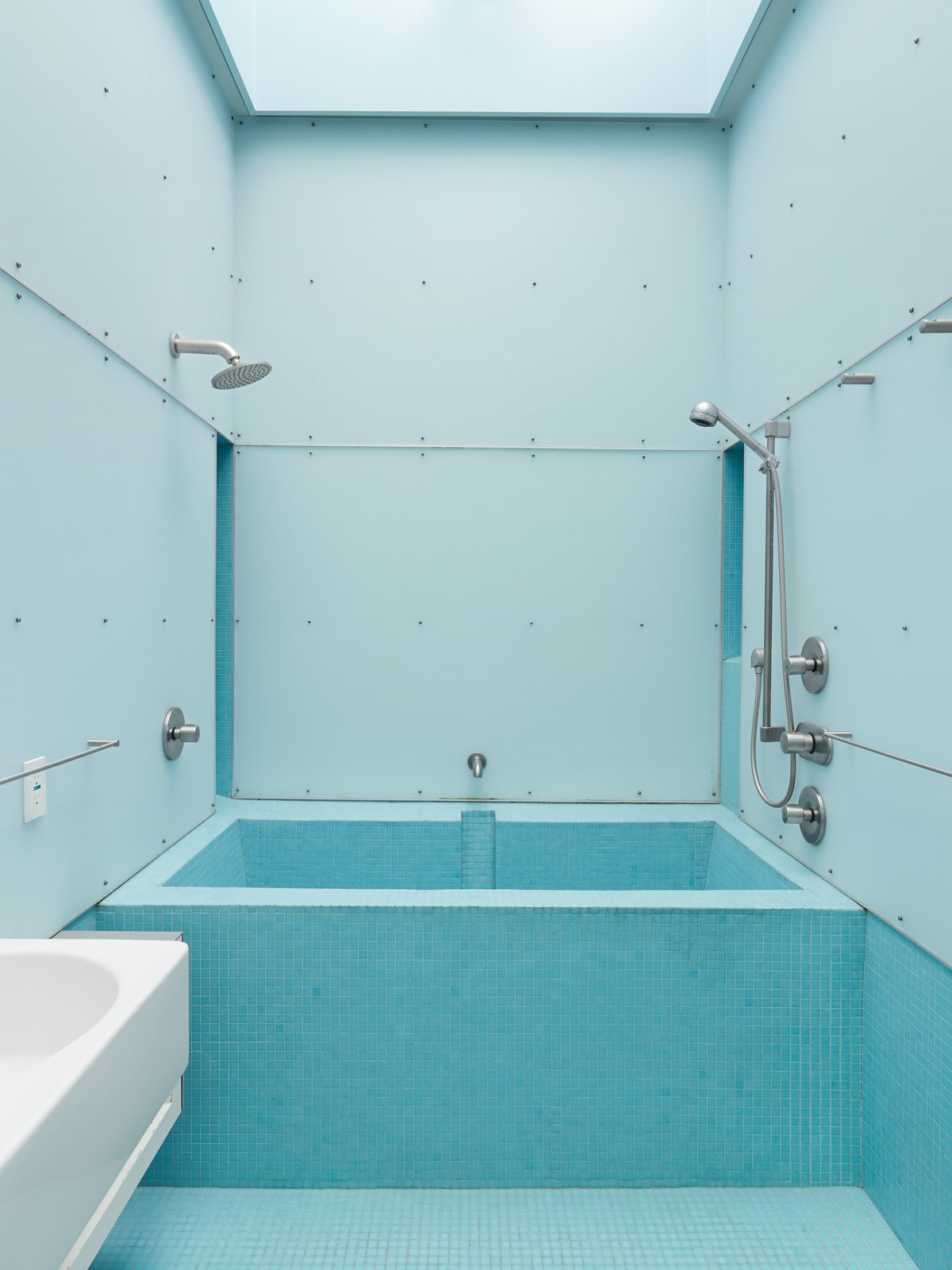 Dunbar describes the bathroom as an outside-in room because it has light, air, and sometimes, when it drizzles and the skylight left open, even rain. Designed for exactly these circumstances, a blue-glass mosaic tile floor is laid at an angle to drain with ease.