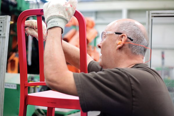 A worker smoothes any imperfections before manually installing the H-brace.