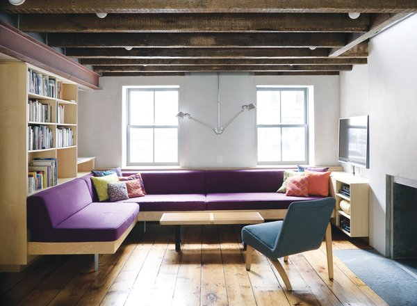 Facing the front facade on the English basement level, a sectional of Dixon's design punctuates the otherwise neutral hues with a stately purple. The lamp is a double-suspension Tolomeo from Artemide. The reupholstered Thonet chair lends balance to the room through its own asymmetry.