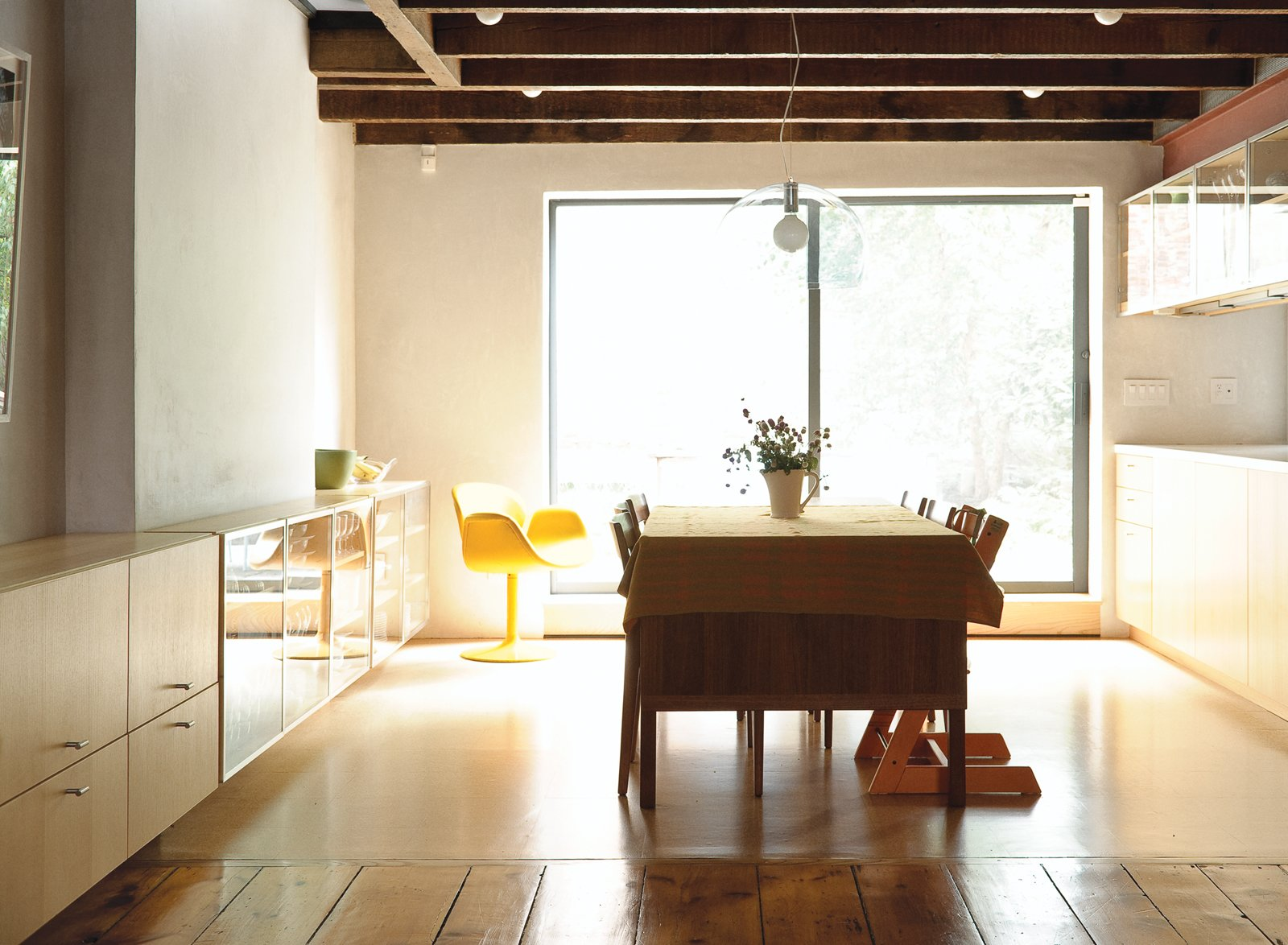 Brightened by light from the backyard, the built-in credenzas and kitchen cabinetry are by JKK Woodcraft. A Kartell FL/Y pendant lamp bridges the glass and wood details. Tagged: Dining Room, Table, Pendant Lighting, Chair, and Medium Hardwood Floor.  Photo 2 of 28 in Family Home Renovation in Brooklyn