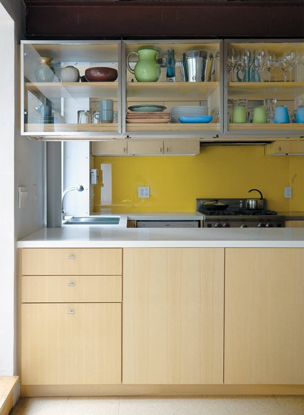 Lange's collection of vintage Heath cups and saucers, Jasper Morrison White Moon dinnerware for Rosenthal, and Simon Pearce handblown goblets fill the overhead kitchen cabinets, which are accessible from either side of the counter. The yellow backsplash is back-painted glass.