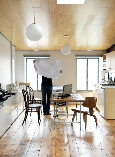 Dixon inspects a drawing in the couple's shared office on the home's top floor. The space features a sloping ceiling that rises to ten feet at one end. The new wood of the inserted ceiling counterpoints the vintage pumpkin pine floorboards underfoot.