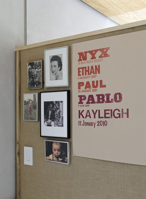 Family pictures and a letterpress poster by Lange's mother, designer Martha Scotford, adorn a textile covered panel.