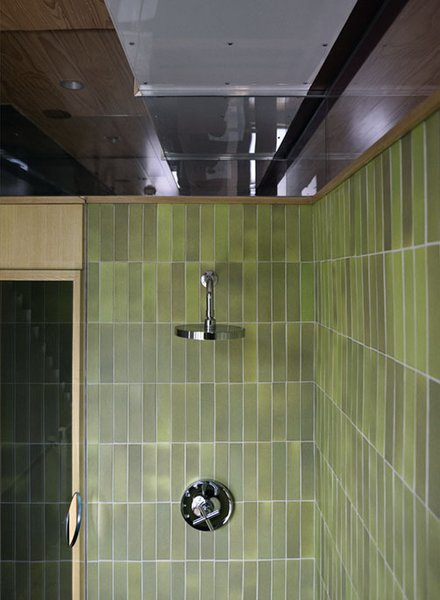 Green Heath tile, with their signature unevenness, provide a warm touch to the modern space. A cut-out in the glass allows the bather to dial in the right temperature on the Kohler fixture before stepping into the shower.