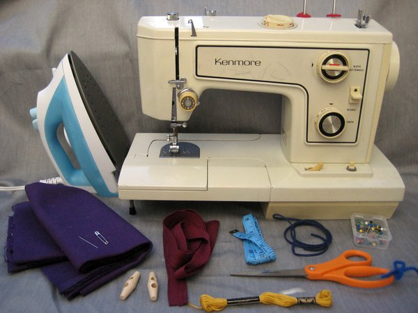 Here are the materials you need to make it happen:<br><br>-iron<br><br>-sewing machine<br><br>-straight pins<br><br>-scissors<br><br>-approximately 1/4 yard faux suede cord (it's the blue one there)<br><br>-embroidery thread<br><br>-measuring tape<br><br>-approximately 1/4 yard twill tape (or any kind of tie for the top, really: hemp or cotton cord, a few strands of ric-rac, whatever you like)<br><br>-two buttons<br><br>-1/3 yard fabric. Lots of types will work, but I chose a mid-weight cotton twill (a previous sling in linen was a little light)<br><br>-needle<br><br>-safety pin (the bigger/sturdier the better)